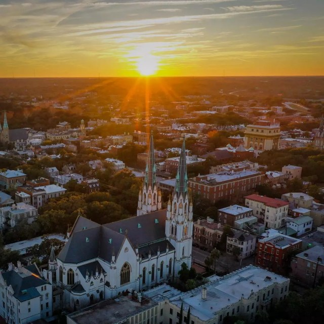 Sunrise over church and buildings in Savannah. Photo by Instagram user @riverrat_productions