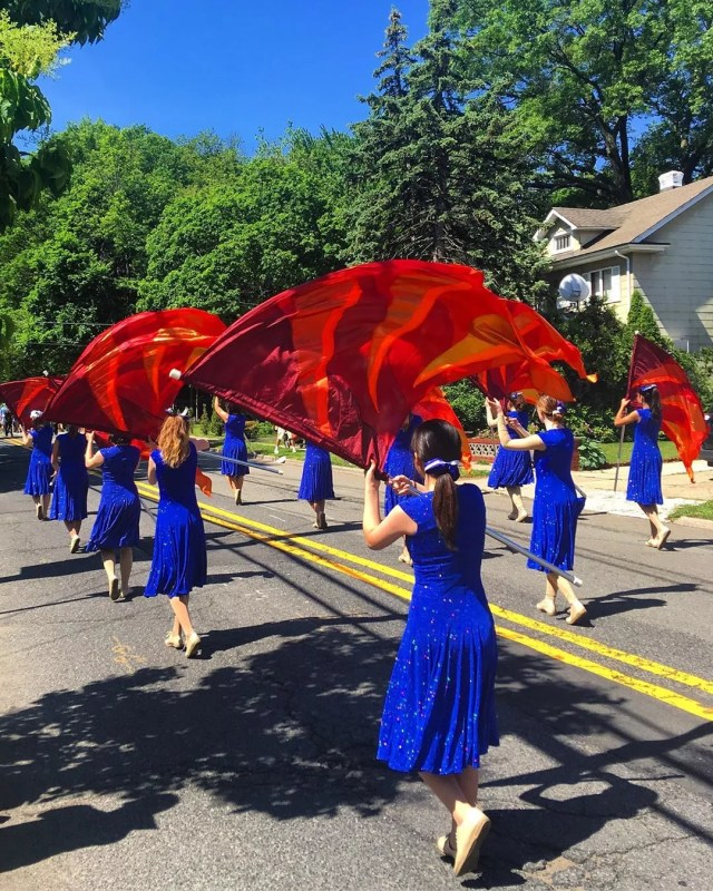 Girls waving red flags in parade. Photo by Instagram user @cap_one60