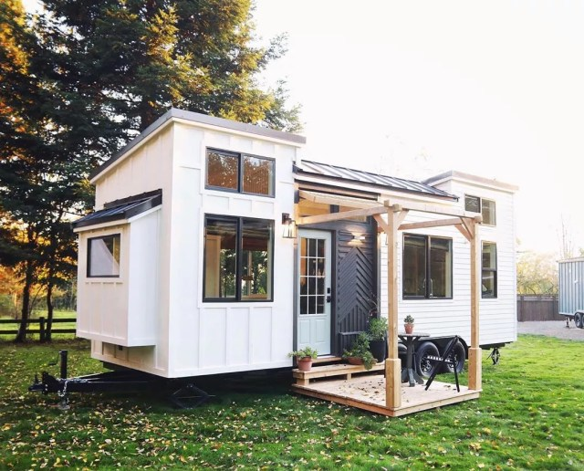 White tiny home with black doors and porch. Photo by Instagram user @handcraftedmovement