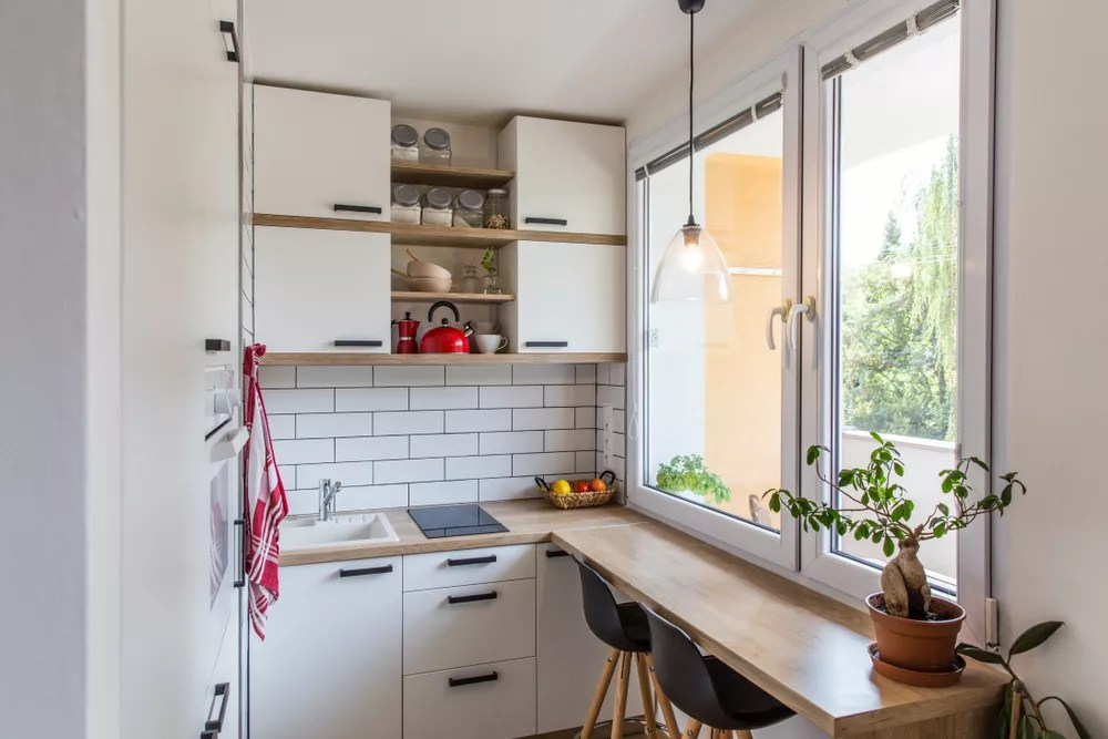 Tiny home kitchen with white wall and white cabinets.