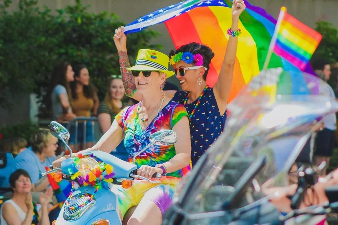 Two women holding rainbow flags riding a scooter. Photo by Instagram user @showtimechamaco