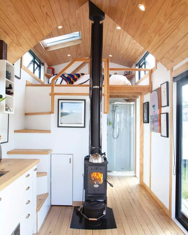 Tiny home with white walls and a black wood furnace. Photo by Instagram user @camandas_tinyhouse