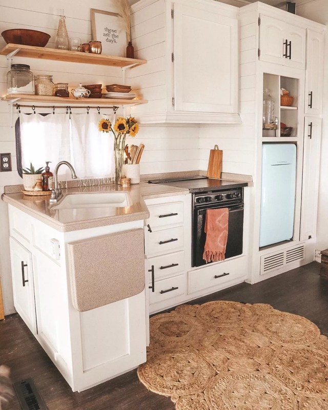 Tiny home kitchen with white cabinets and light blue fridge. Photo by Instagram user @shelbyadrift