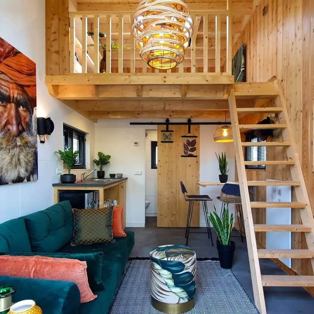 Tiny home with wood loft and green decor. Photo by Instagram user @tinyhousesdroomparken