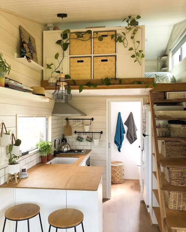 Tiny home with all white walls and plants hanging from ceiling. Photo by Instagram user @girlinatinyhouse