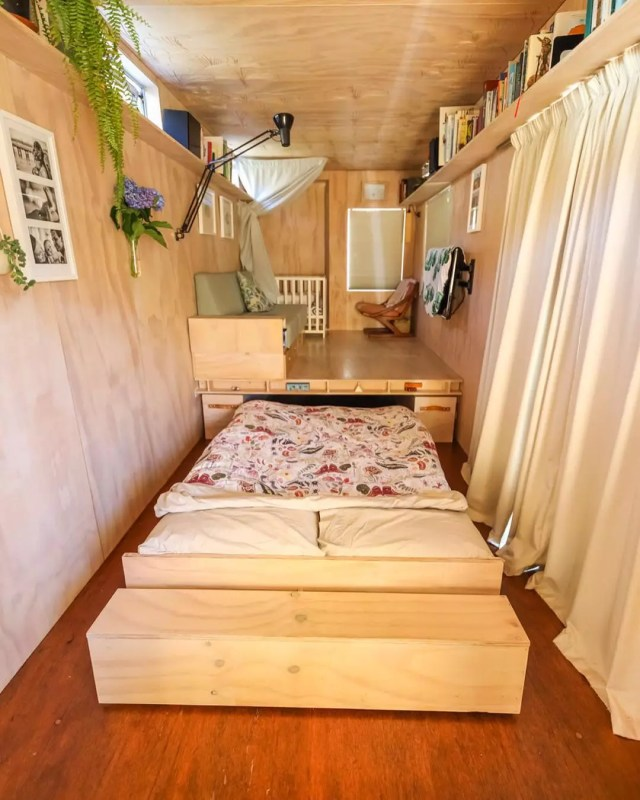 Tiny home with wood walls and pullout bed. Photo by Instagram user @livingbiginatinyhouse