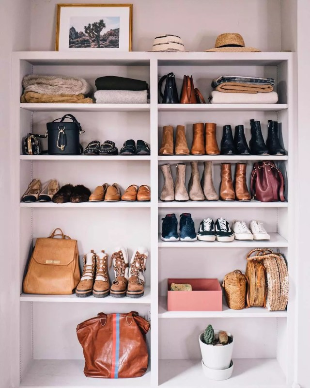 Boots and clothes sitting on white shelves. Photo by Instagram user @jessannkirby