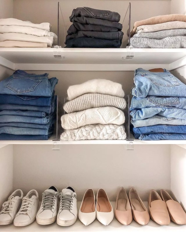 Sweaters and jeans folded on shelves. Photo by Instagrma user @girlmeetsgold