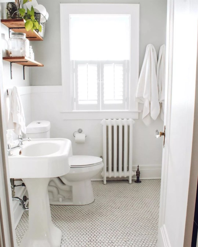 Small, all-white bathroom with wood shelves. Photo by Instagram user @thelittlebylittlehome_