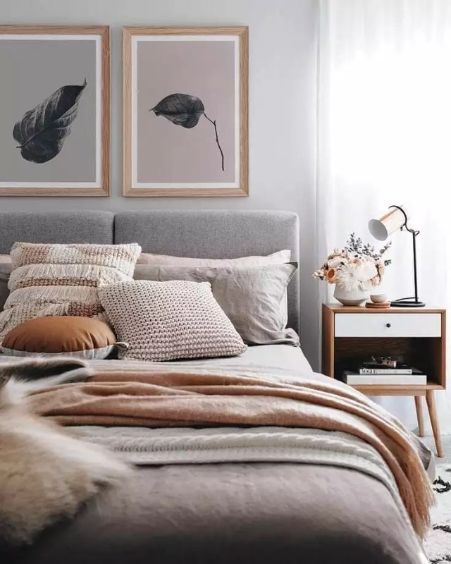 Gray bedroom with light pink pillows and leaf paintings. Photo by Instagram use @ugs_beddings