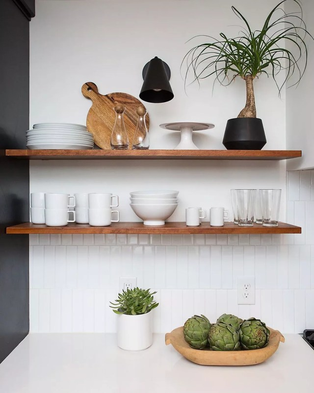 Dark wood floating shelves with white dishes on them. Photo by Instagram user @adidstudio