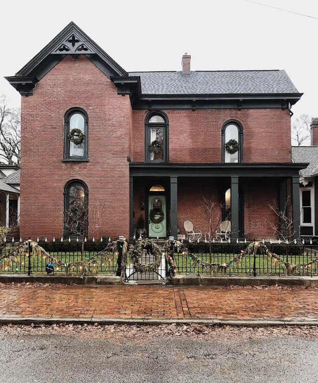 Two-story red brick house with black trim and wrought iron fence. Photo by Instagram user @hollyvioletragsdale