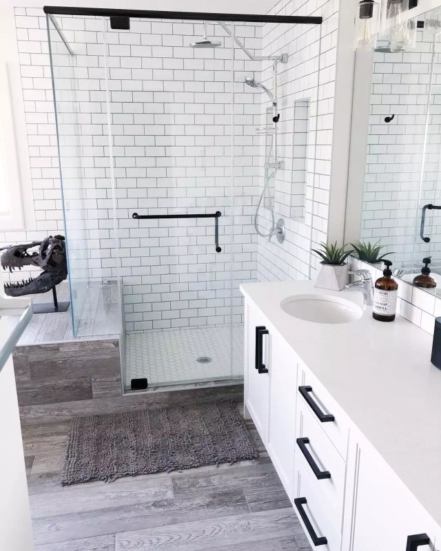 White-tile bathroom with wood floors and glass shower. Photo by Instagram user @kling_designs