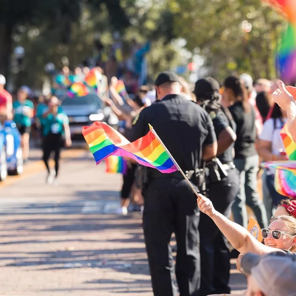 People holding rainbow flags at parade. Photo by Instagram user @comeoutwithpride