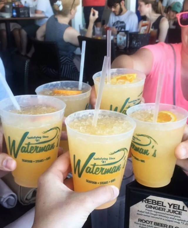 Group of people cheersing orange cocktails. Photo by Instagram user @watermanssurfsidegrille