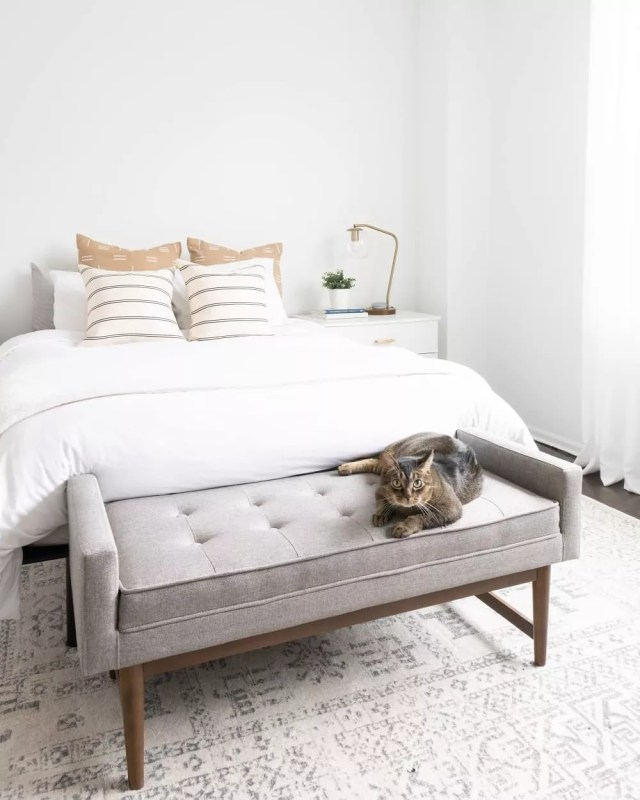 White bedroom with white bed and cat on gray bench. Photo by Instagram user @vivandtim.home