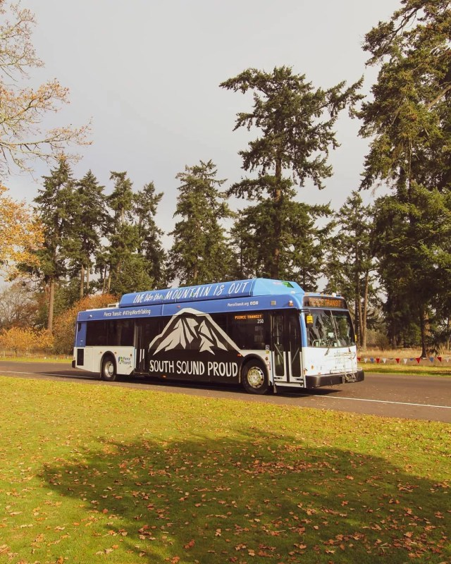 Blue and black bus driving by trees. Photo by Instagram user @piercetransit