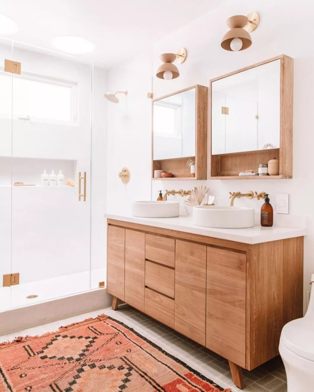 White bathroom with wood cabinet and orange rug. Photo by Instagram user @jeffmindell