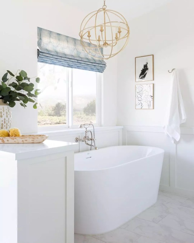 White bathroom with large white tub and golden sphere light fixture. Photo by Instagram user @amybartiam