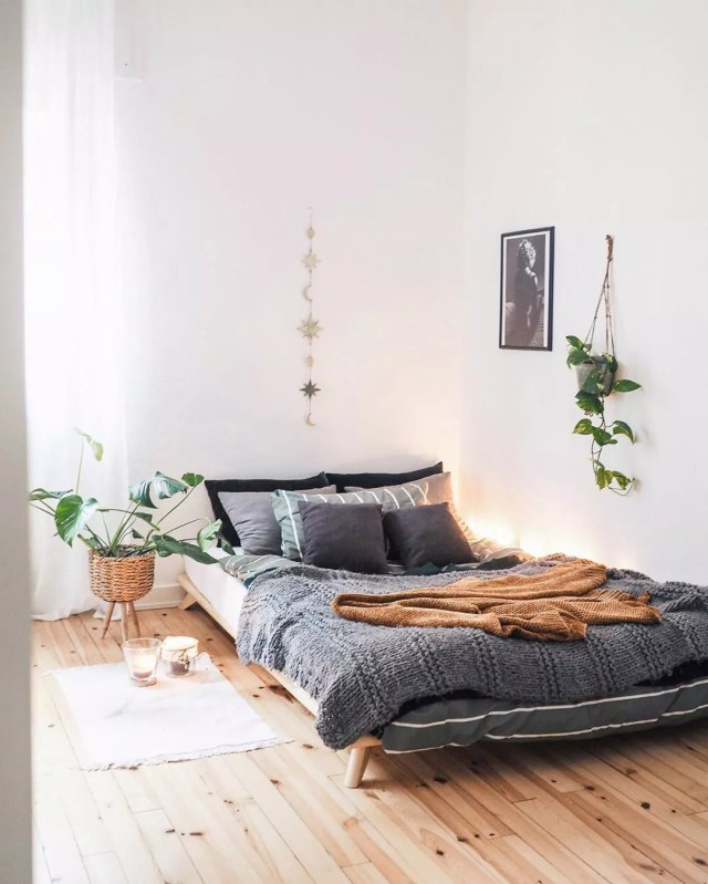 White bedroom with gray bed, plants, and wood floors. Photo by Instagram user @what.the.hygge