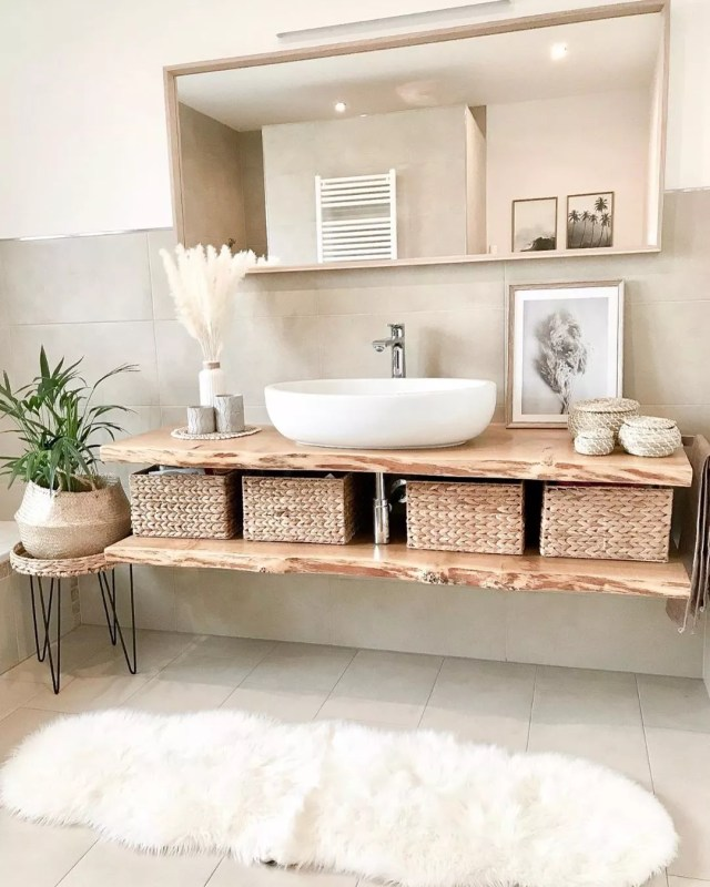 White bathroom with wood floating cabinet and white faux fur rug. Photo by Instagram user @kati_home13