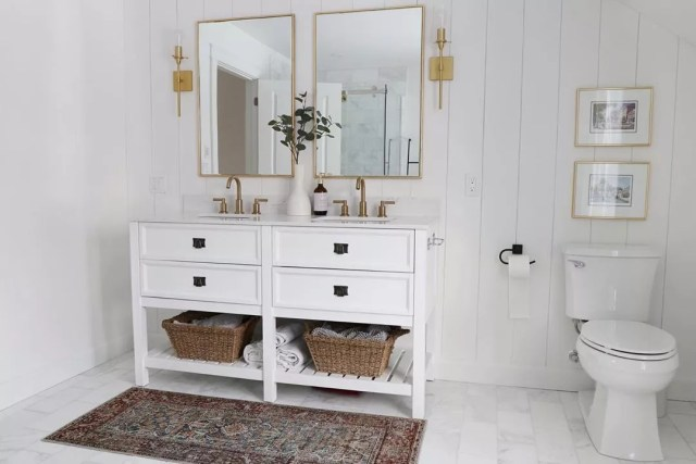 All white bathroom with gold light fixtures and wicker baskets under white cabinet. Photo by Instagram use @househappening