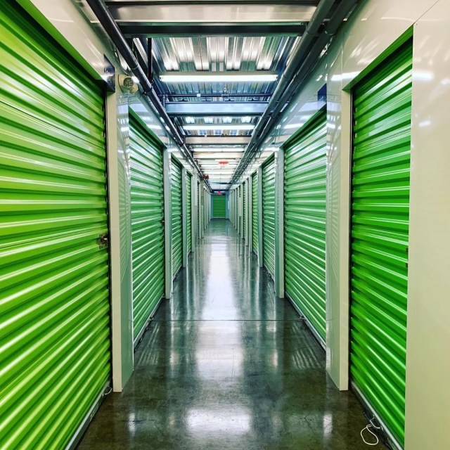 Hallway of storage units with green doors. Photo by Instagram user @tentpitcher