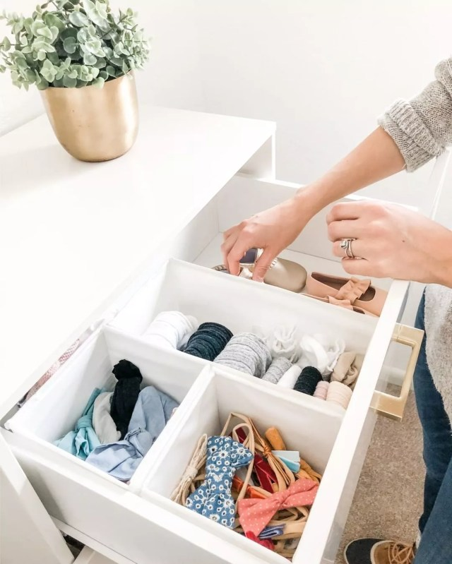 dresser drawer filled with baby clothes with drawer organizers photo by Instagram user @britneetanner