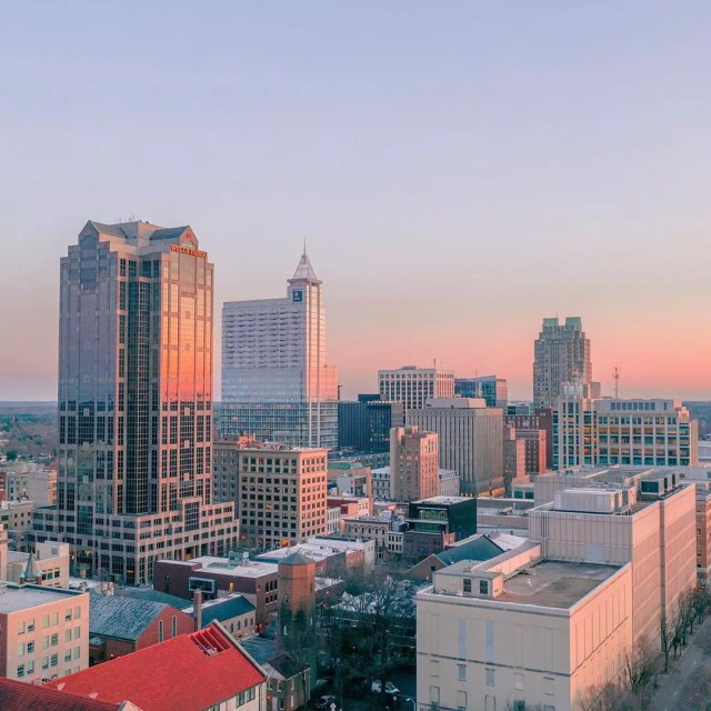 downtown Raleigh, NC at dusk with skyline photo by Instagram user @dyyymondaerials