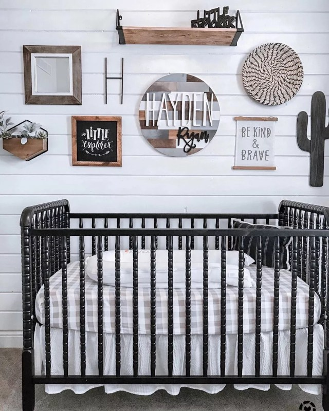 Black crib by wall with decor. Photo by Instagram user @mymodularfarmhouse