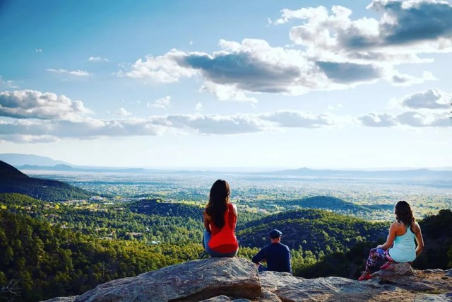 people sitting on rocks looking out over lindo in Santa Fe photo by Instagram user @cityofsantafe