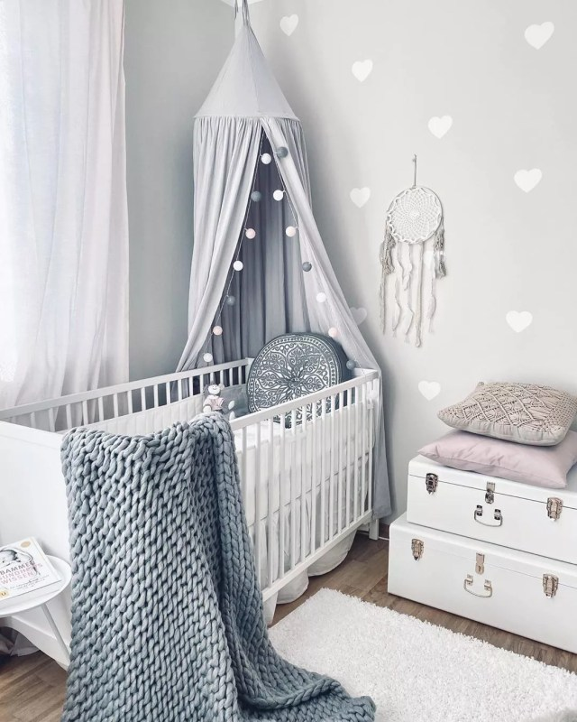 Gray baby room with white hearts and white furniture. Photo by Instagram user @girlsbabyroom