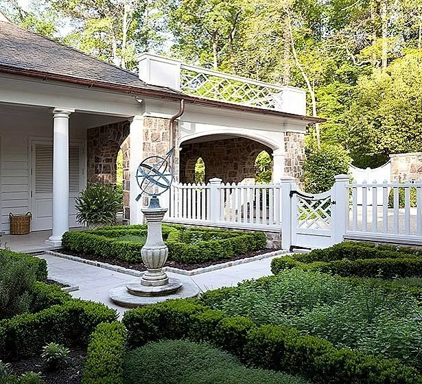 backyard landscaping with sun dial and white fence surrounding short shrubs photo by Instagram user @johnbaranellodesign