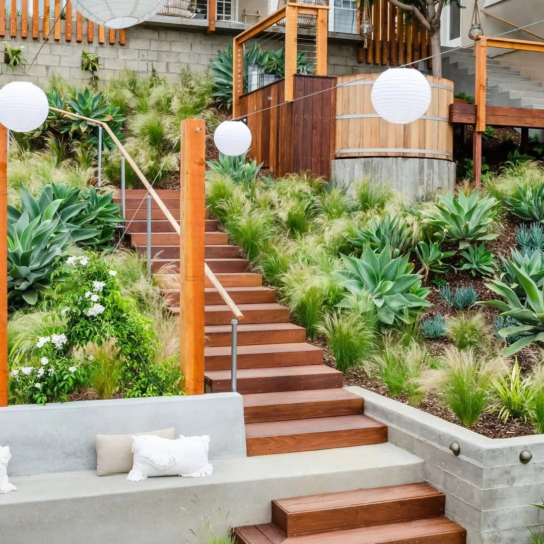 backyard landscaping with wooden stairs and native plants surrounding a small sitting area with lanterns strung above photo by Instagram user @brookside_design