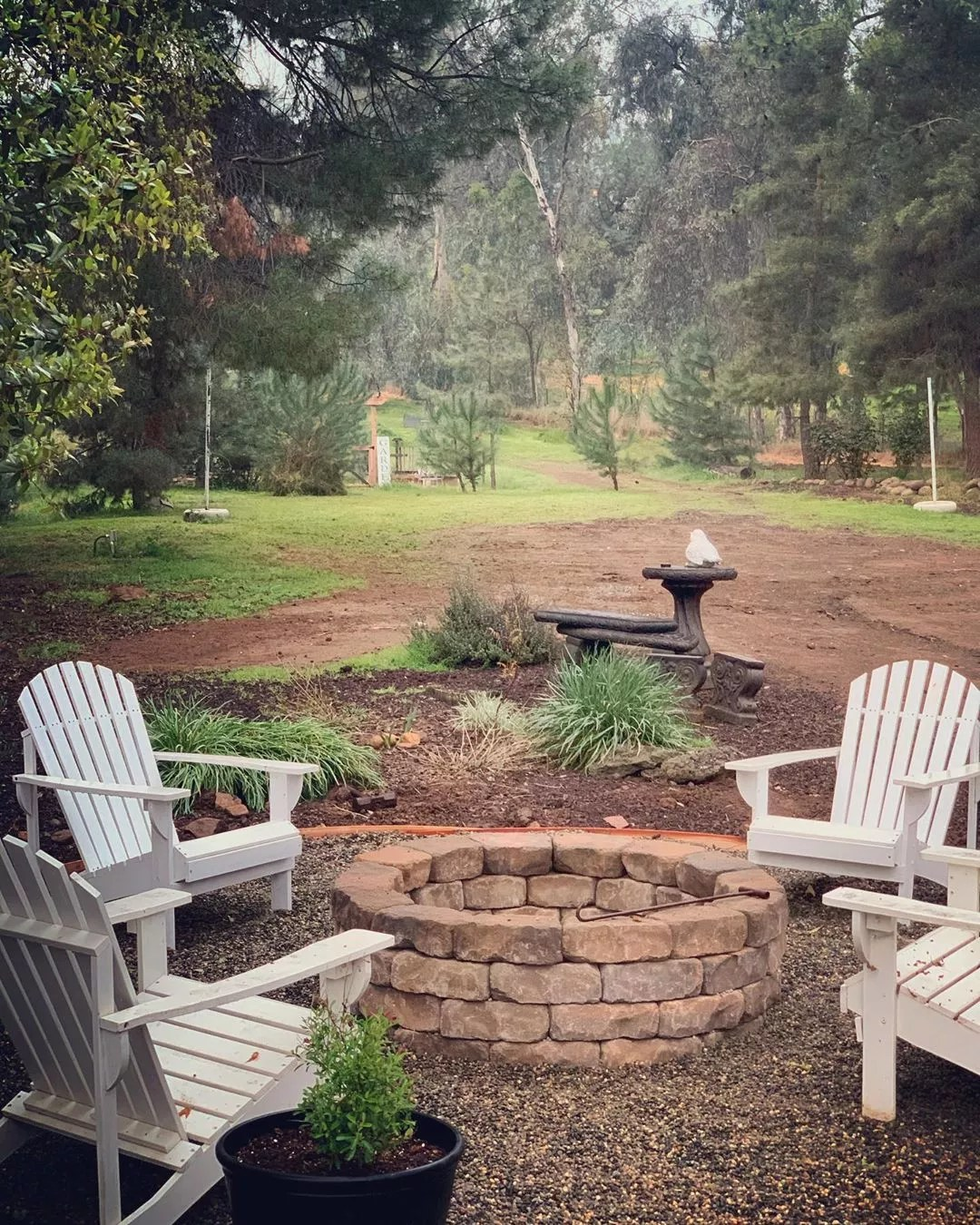 backyard fire pit built with large stones and white adirondack chairs around photo by Instagram user @claudio_paisagismo