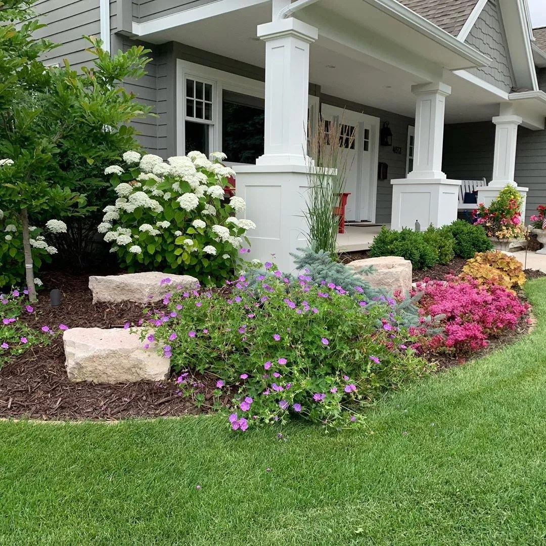front landscaping with multiple plant types and layers with a bed of mulch photo by Instagram user @sarah.lloyd.landscape.design
