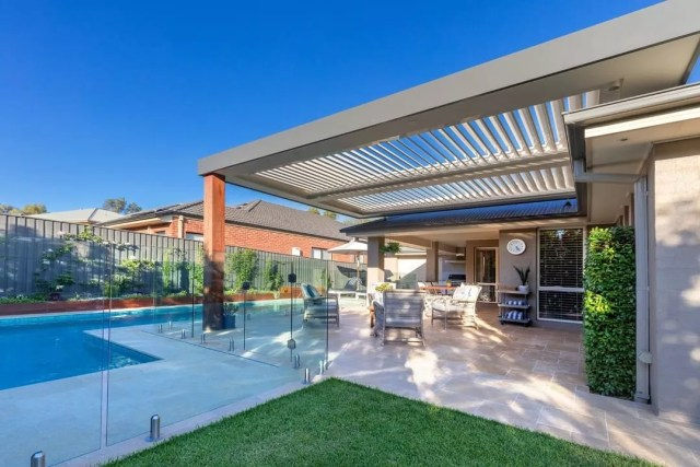 large home with big pergola over head and pool around photo by Instagram user @opening_roof_specialists