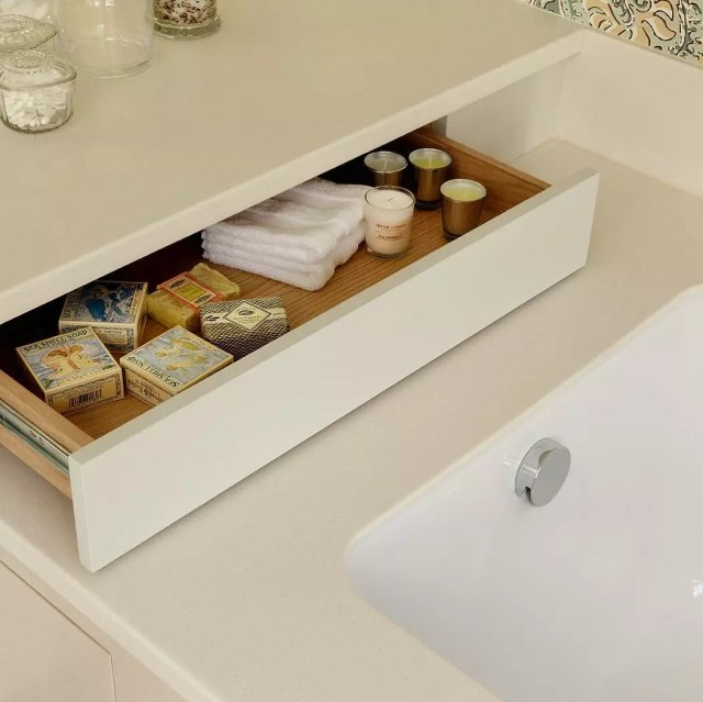 Drawer added underneath an overhanging counter near bathtub. Photo by Instagram user @cueandco