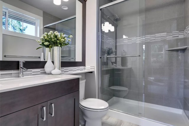 renovated bathroom with zero entry shower and large mirror