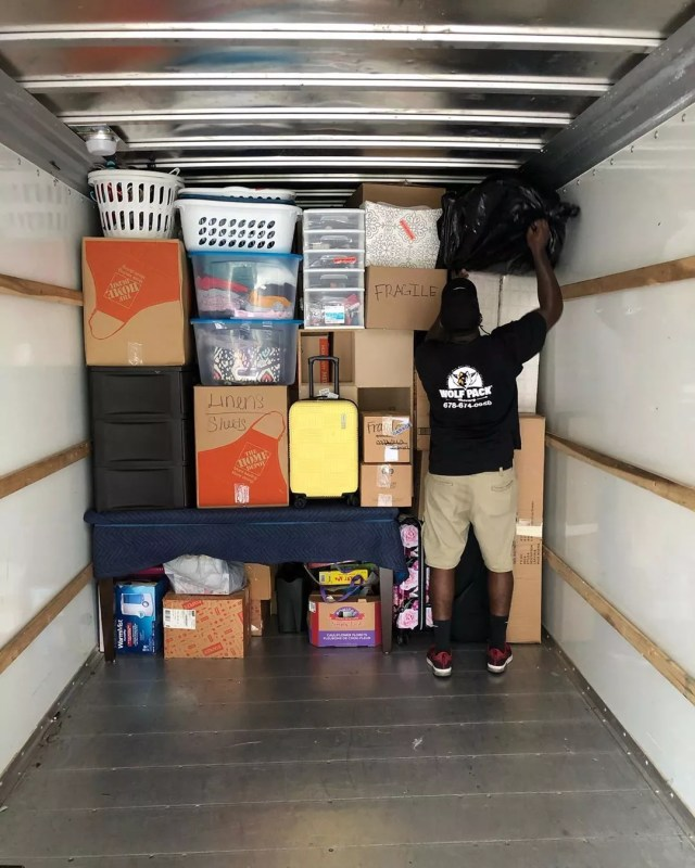 Man Packing Boxes into Moving Truck. Photo by Instagram user @wolfpackmovers