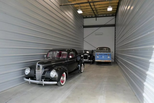Multiple Classic Cars Parked in a Drive-Up Storage Unit. Photo by Instagram user @elitestor_st.rose