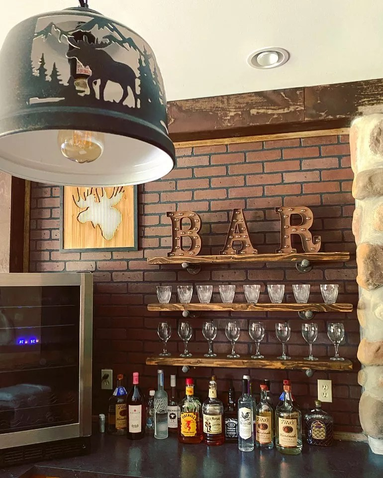 Basement Bar with Faux Bricks and Gas Pipe Shelving. Photo by Instagram user @thelittleblueranch