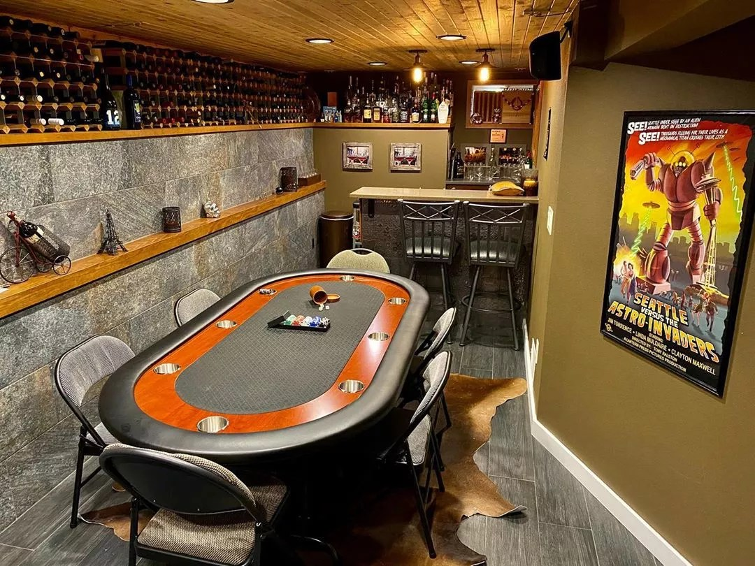 Basement Poker Table Set Up with Wine Racks on the Wall and a Bar. Photo by Instagram user @bubbleandbrown