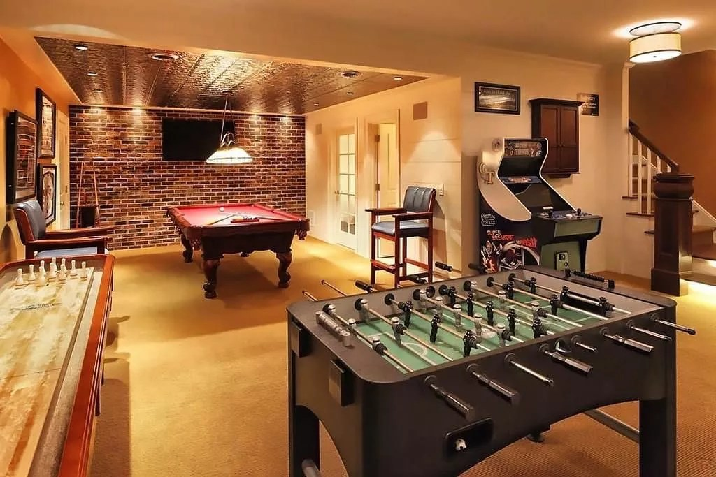 Finished Basement Filled with a Pool Table, Shuffleboard Table, Foosball, and Arcade Game. Photo by Instagram user @mancavemasters
