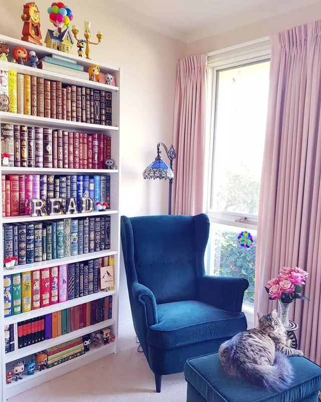 Reading Area with a Blue Chair and a Tall Bookcase Organized by Color. Photo by Instagram user @enchanted_bookshelf