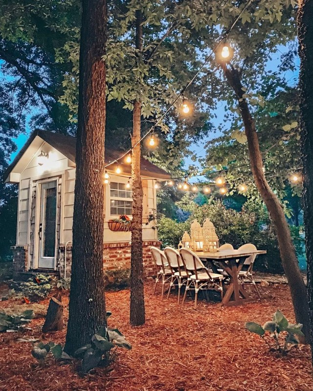 Small She Shed in the Trees with a Table and Chairs Nearby. Photo by Instagram user @cottonstem