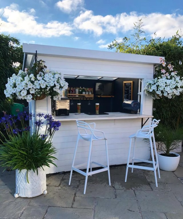 Small White Bar She Shed with White Stools in Front. Photo by Instagram user @houseonthedales