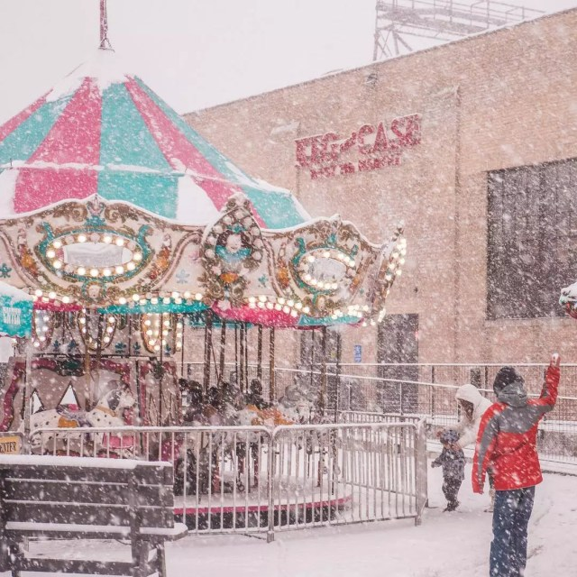 Kid Throwing a Snowball In Front of a Carousel in the Snow. Photo by Instagram user @emilyjaneandco
