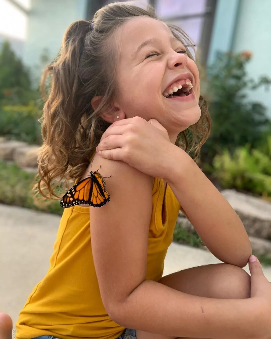 Little Girl Laughing with a Butterfly on her Arm. Photo by Instagram user @butterflyworldflorida