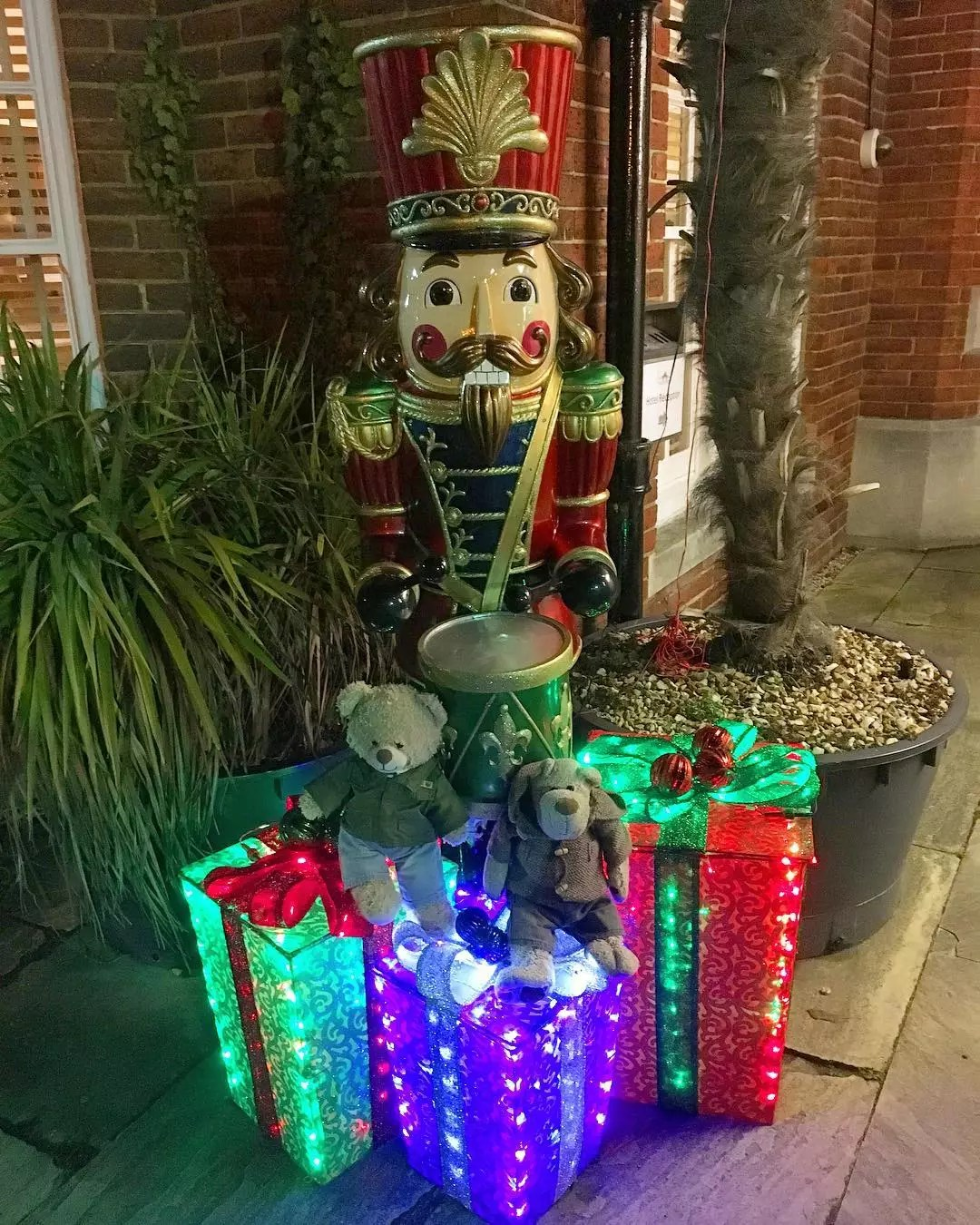 DIY presents created with a wooden frame and mesh material glow with lights outside in front of a large nutcracker. Photo by Instagram user @tedandalfiebears.
